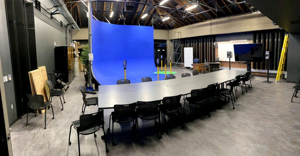 Studio with blue cyc wall and long table with chairs.