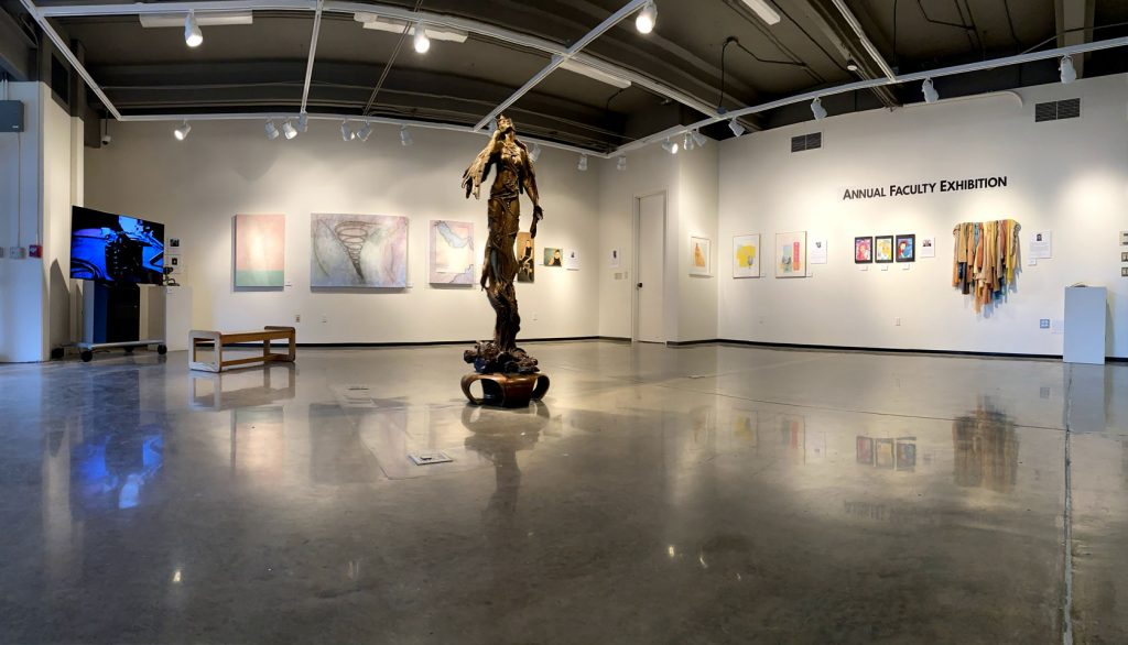 sculpture of winged female figure amidst art gallery