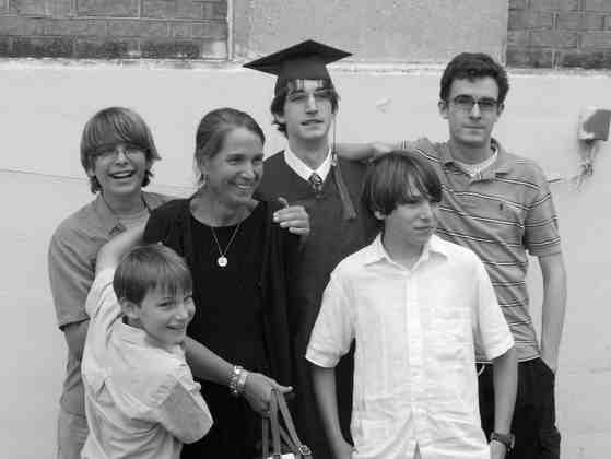 four boys stand with mother, one wears a graduation cap