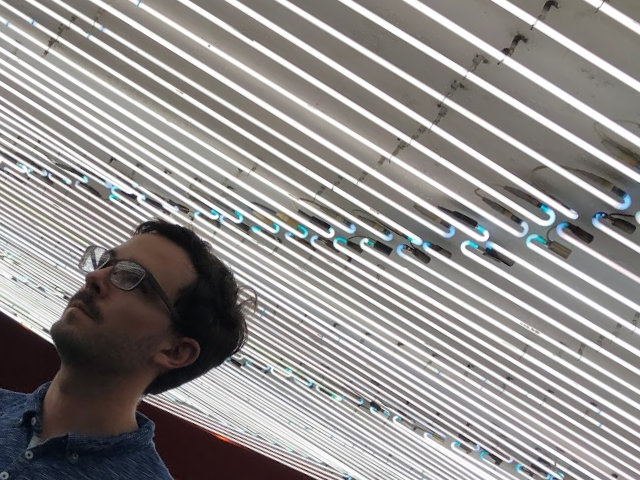 man's face under neon lights spanning the ceiling